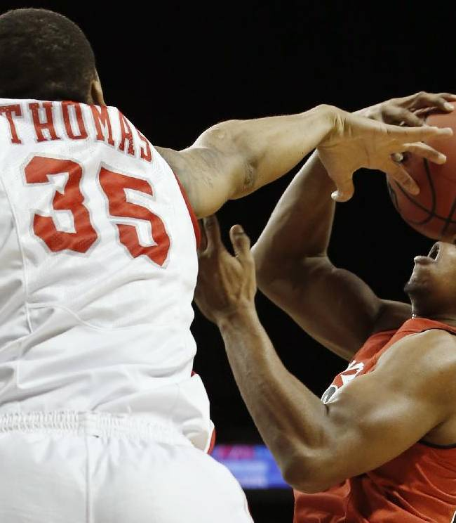 Houston forward TaShawn Thomas (35) gets his hand on the ball as Texas Tech guard Toddrick Gotcher (20) goes up for a layup in the first half of their NCAA college basketball game, the consolation game of the Legends Classic, Tuesday, Nov. 26, 2013, in New York