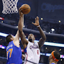 Los Angeles Clippers' DeAndre Jordan, center, shoots over New York Knicks' Andrea Bargnani, of Italy, left, and Carmelo Anthony, right, during the first half of an NBA basketball game in Los Angeles, Wednesday, Nov. 27, 2013 The Associated Press