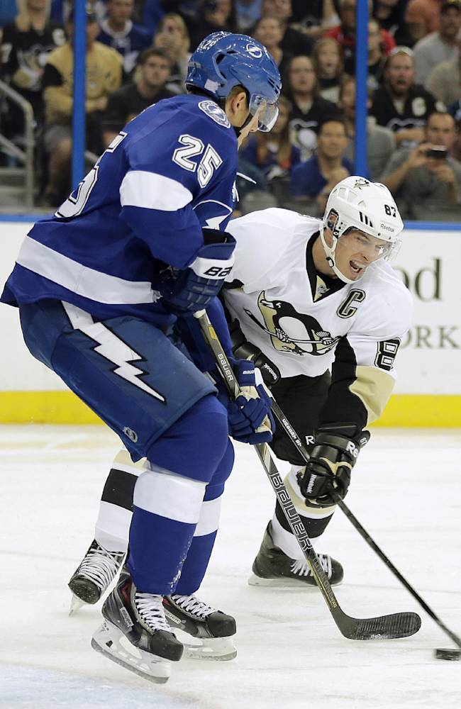 Pittsburgh Penguins center Sidney Crosby (87) struggles to get off a shot in front of Tampa Bay Lightning defenseman Matt Carle (25) during the first period of an NHL hockey game on Saturday, Oct. 12, 2013, in Tampa, Fla