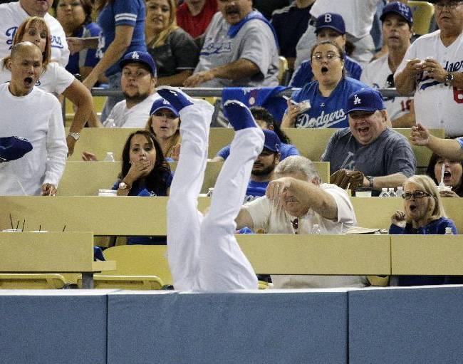 CORRECTS NAME OF PLAYER THAT FOULED OUT AS BRIAN MCCANN NOT JUSTIN UPTON - Fans react as Los Angeles Dodgers left fielder Carl Crawford falls upside down over the rail after catching a foul ball hit by Atlanta Braves' Brian McCann during the seventh inning in Game 3 of the National League division baseball series Sunday, Oct. 6, 2013, in Los Angeles