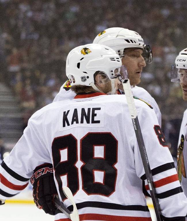 Chicago Blackhawks' Patrick Kane (88) is congratulated by Marian Hossa, center, and Duncan Keith after Kane scored against the Toronto Maple Leafs during the first period of an NHL hockey game in Toronto on Saturday, Dec. 14, 2013