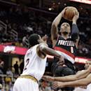 Portland Trail Blazers' Damian Lillard (0) jumps to the basket against Cleveland Cavaliers' Kyrie Irving (2) during the first quarter of an NBA basketball game Tuesday, Dec. 17, 2013, in Cleveland. (AP Photo/Tony Dejak)
