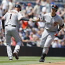 San Francisco Giants' Buster Posey, right, is congratulated by third base coach Tim Flannery after blasting a two run homer against the San Diego Padres in the first inning a baseball game Sunday, April 20, 2014, in San Diego The Associated Press