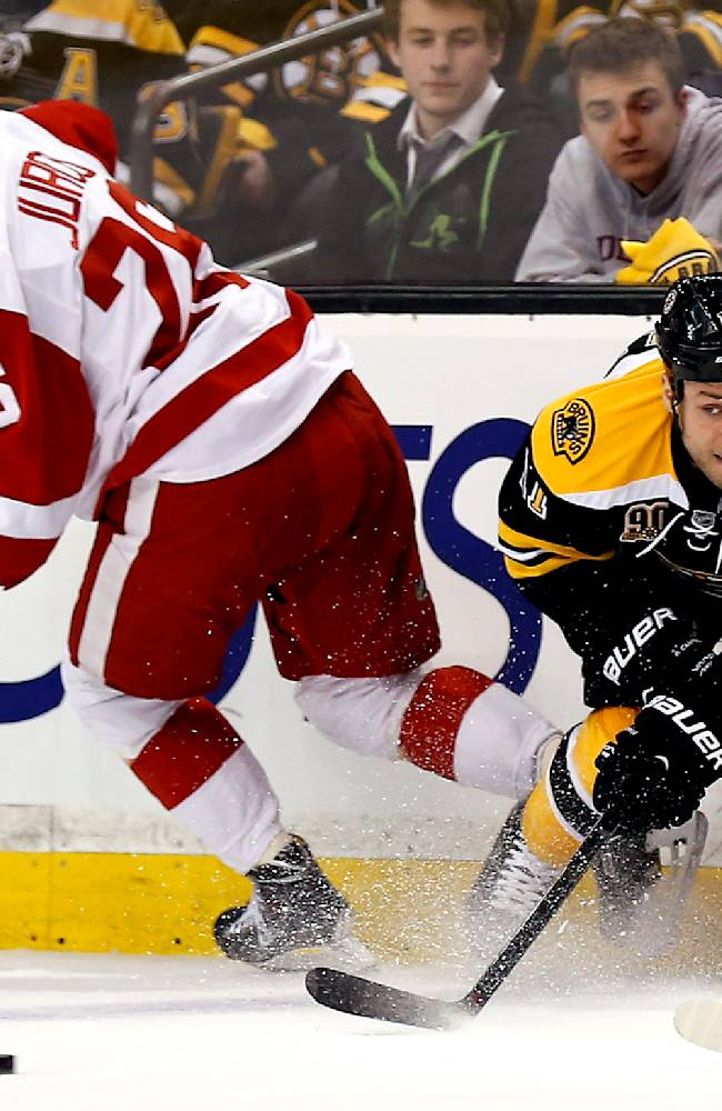Boston Bruins' Gregory Campbell clears the puck away from Detroit Red Wings' Tomas Jurco (26) during the first period of Game 1 of a first-round NHL playoff hockey series in Boston on Friday, April 18, 2014