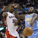Toronto Raptors' Terrence Ross, left, fouls Denver Nuggets' Nate Robinson during the first half of an NBA basketball game on Sunday, Dec. 1, 2013, in Toronto The Associated Press