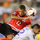Trinidad & Tobago forward Darryl Roberts (12) goes over the back of Honduras defender Orlin Peralta (12) for a header in the second half a CONCACAF Gold Cup soccer match on Monday, July 15, 2013, in Houston. Trinidad & Tobago defeated Honduras 2-0.(AP Photo/Bob Levey)