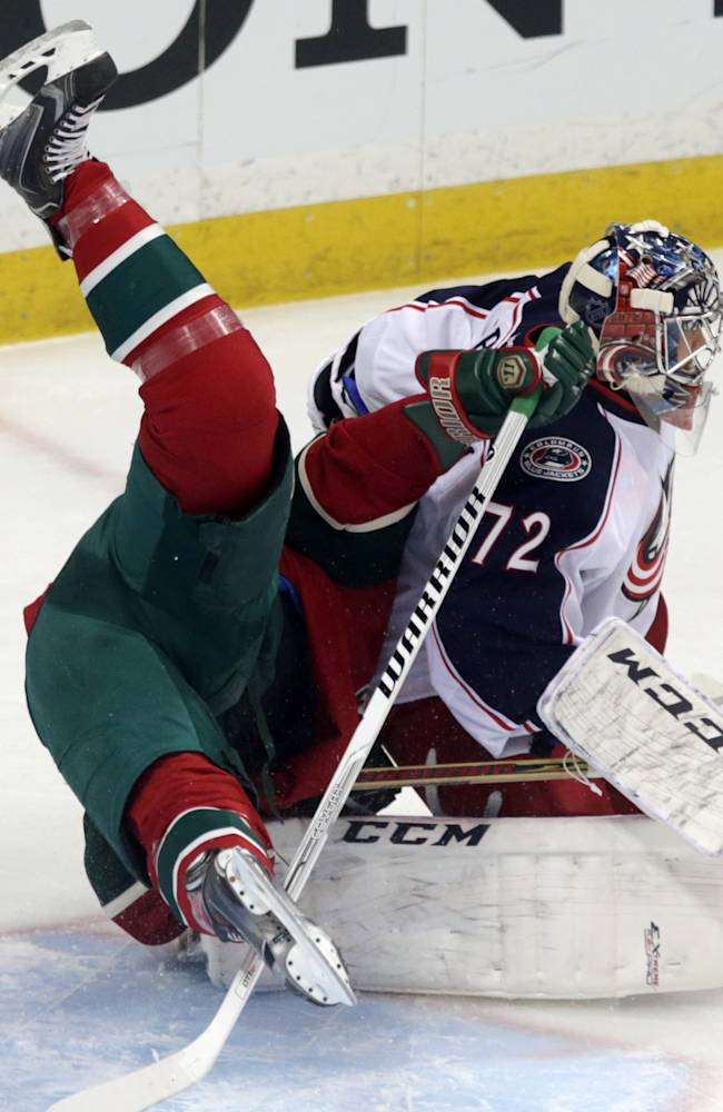 Minnesota Wild's Matt Cooke, left, topples over Columbus Blue Jackets goalie Sergei Bobrovsky, of Russia, in the first period of an NHL hockey game, Saturday, March 15, 2014, in St. Paul, Minn