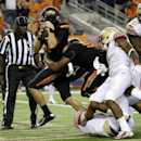 Oklahoma State quarterback J.W. Walsh rumbles past Florida State defenders into the end zone for a touchdown in the second half of an NCAA college football game, Saturday, Aug. 30, 2014, in Arlington, Texas. FSU won 37-31 The Associated Press