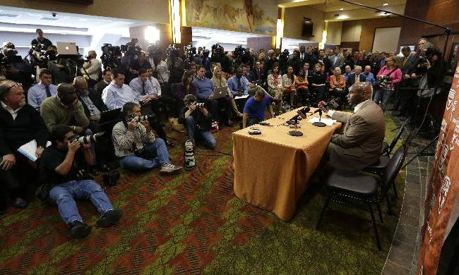 Charlie Strong, right, answers questions during a news conference where he was introduce as the new Texas NCAA college football coach, Monday,  Jan. 6, 2014, in Austin, Texas. He replaces Mack Brown, who coached Texas for 16 years and won the 2005 national championship. Strong spent the previous four years at Louisville