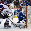 Colorado Avalanche's Jamie McGinn, left, is stopped by Vancouver Canucks goalie Jacob Markstrom, of Sweden, during the first period of an NHL hockey game Thursday, April 10, 2014, in Vancouver, British Columbia The Associated Press