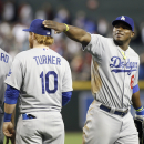 Los Angeles Dodgers' Yasiel Puig, right, congratulates teammates Carl Crawford (3) and Justin Turner (10) after they defeated the Arizona Diamondbacks 8-6 in a baseball game on Sunday, April 13, 2014, in Phoenix The Associated Press