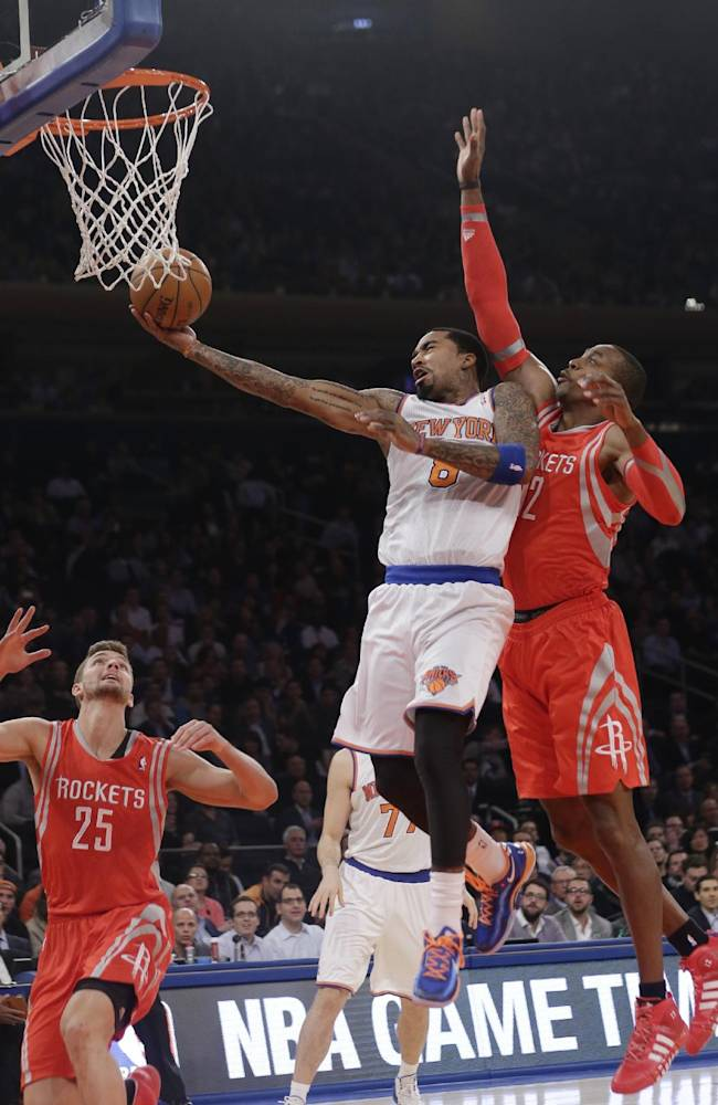 New York Knicks' J.R. Smith (8) drives past Houston Rockets' Dwight Howard (12) and Chandler Parsons (25) during the first half of an NBA basketball game Thursday, Nov. 14, 2013, in New York