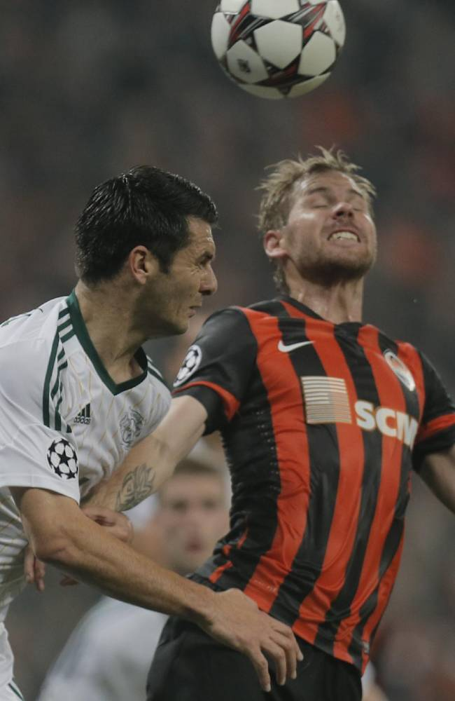 Donetsk's Tomas Hubschman, right, and Leverkusen's Emir Spahic in action for a high ball during the Champions League group A soccer match between Bayer 04 Leverkusen and FC Shakhtar Donetsk  at the Donbas Arena stadium in Donetsk, Ukraine, Tuesday, Nov. 5, 2013