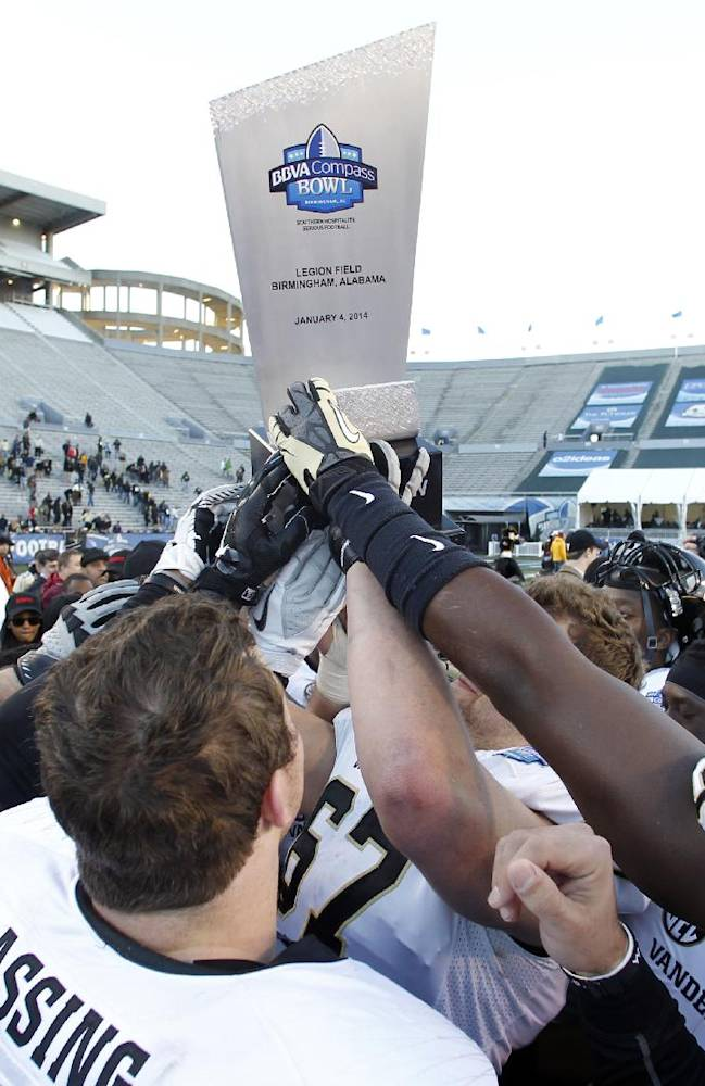 Vanderbilt players hold up the trophy after defeating Houston 41-24 in the BBVA Compass Bowl NCAA college football game on Saturday, Jan. 4, 2014, in Birmingham, Ala