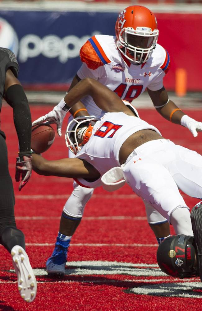 Sam Houston State's Yedidiah Louis (9) falls backward for a gain against Eastern Washington in the first half of an NCAA college football game in Cheney, Wash., Saturday, Aug. 23, 2014
