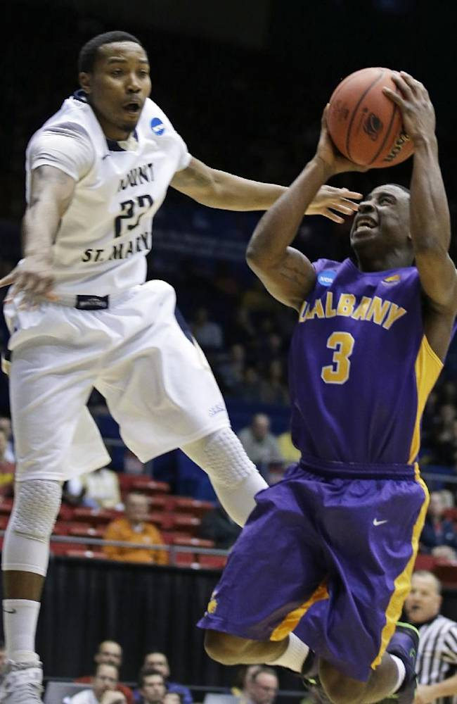 Albany guard DJ Evans (3) drives against Mount St. Mary's guard Julian Norfleet in the first half of a first-round game of the NCAA college basketball tournament, Tuesday, March 18, 2014, in Dayton, Ohio
