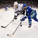 Vancouver Canucks' Henrik Sedin, right, of Sweden, tries to stick handle around San Jose Sharks' Justin Braun during the first period of an NHL hockey game, Thursday, Nov. 14, 2013 in Vancouver, British Columbia The Associated Press