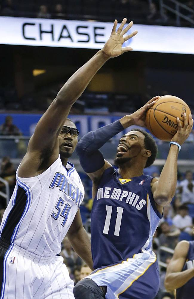Memphis Grizzlies' Mike Conley (11) drives to the basket past Orlando Magic's Jason Maxiell (54) during the first half of an NBA preseason basketball game in Orlando, Fla., Friday, Oct. 18, 2013