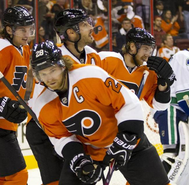 Philadelphia Flyers' Tye McGinn, left, heads back with his teammates; Claude Giroux, foreground, Mark Streit, center top, and Jakub Voracek, second from right, after McGinn scored his second goal past Vancouver Canucks' Roberto Luongo, right, during the second period of a NHL hockey game, Tuesday, Oct. 15, 2013, in Philadelphia