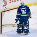Vancouver Canucks goalie Joe Cannata stands near the net after being scored on by San Jose Sharks' Brent Burns during the second period of an NHL preseason hockey game in Vancouver, British Columbia, Tuesday, Sept. 23, 2014. The Associated Press