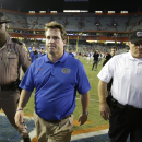 In this Oct. 18, 2014, file photo, Florida head coach Will Muschamp, center, leaves the field after losing to Missouri 42-13 in an NCAA college football game in Gainesville, Fla. With his job on the line, Florida coach Will Muschamp is turning to freshman