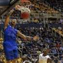 Kansas' Travis Releford (24) dunks over West Virginia's Jabarie Hinds, center, and Eron Harris (10) during the first half of an NCAA college basketball game in Morgantown, W.Va., on Monday, Jan. 28, 2013. (AP Photo/David Smith)