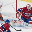 Montreal Canadiens goaltender Dustin Tokarski, right, makes a save against New York Islanders' Brock Nelson (29) as Canadiens' Andrei Markov (79) defends during third-period NHL hockey game action in Montreal, Saturday, Jan. 17, 2015 The Associated Press