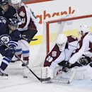 Winnipeg Jets' Evander Kane (9) gets shut down by Colorado Avalanche goaltender Reto Berra (20) and Avalanche's Cory Sarich (16) on the wraparound during the third period of an NHL hockey game, Wednesday, March 19, 2014, in Winnipeg, Manitoba. The Jets wo