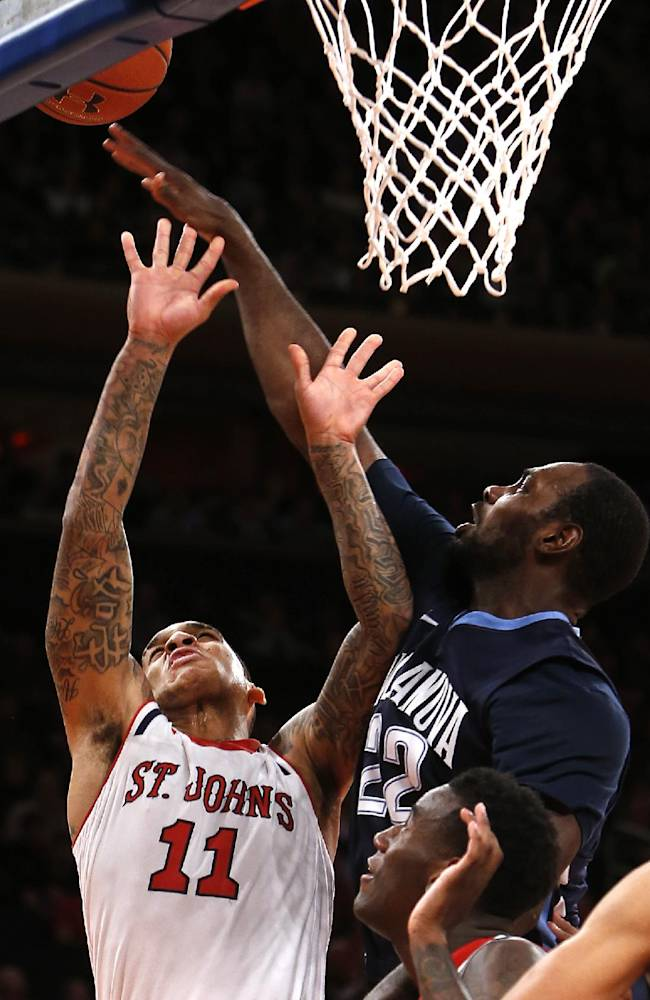St. John's D'Angelo Harrison (11) is fouled as he shoots against Villanova's JayVaughn Pinkston (22) during the second half of an NCAA college basketball game Saturday, Jan. 11, 2014, in New York. Villanova won 74-67