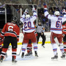 New York Rangers' Chris Kreider (20) and Rick Nash (61) celebrate Kreider's goal as New Jersey Jersey Devils' Andy Greene (6) and goaltender Cory Schneider react during the first period of an NHL hockey game Tuesday, Oct. 21, 2014, in Newark, N.J. (AP Photo/Bill Kostroun)