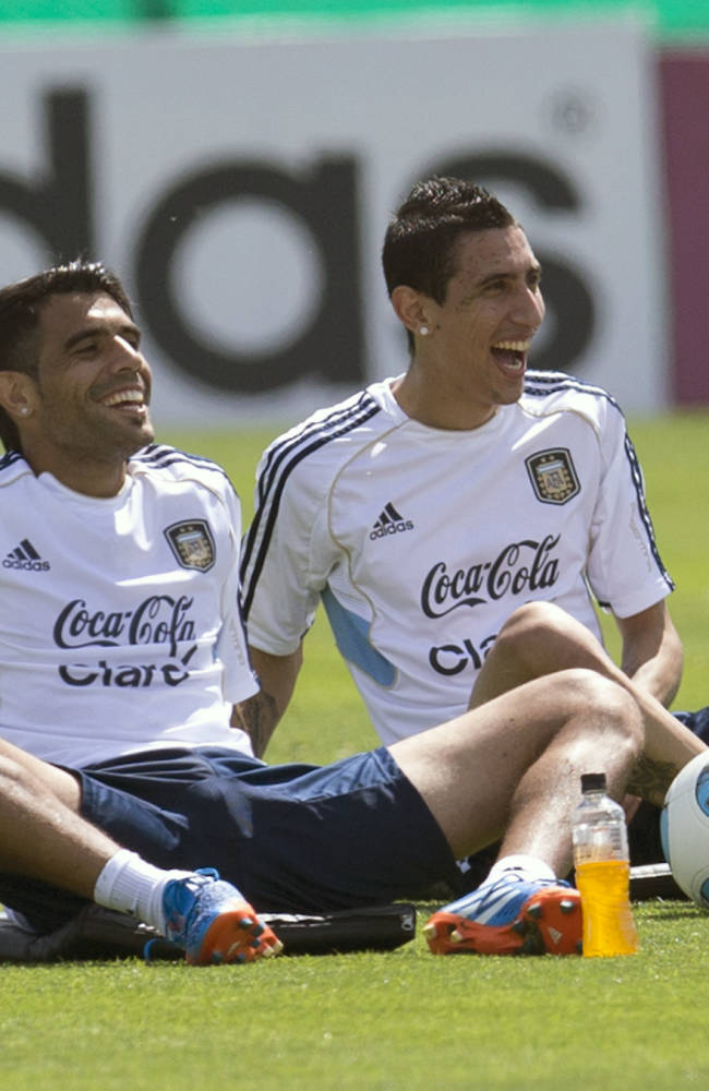 Augusto Fernandez, left, and Angel Di Maria laugh after attending a team training session ahead a Brazil 2014 World Cup qualifying soccer match with Peru in Buenos Aires, Argentina, Tuesday, Oct. 8, 2013