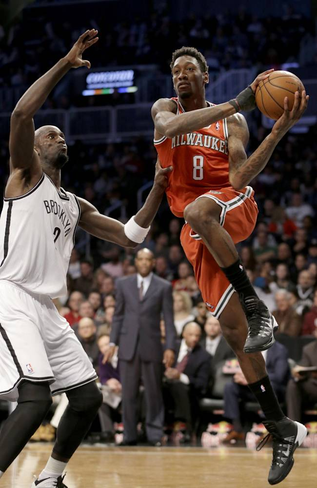 Milwaukee Bucks' Larry Sanders, right, passes around Brooklyn Nets' Kevin Garnett during the first half of an NBA basketball game at the Barclays Center, Friday, Dec. 27, 2013, in New York