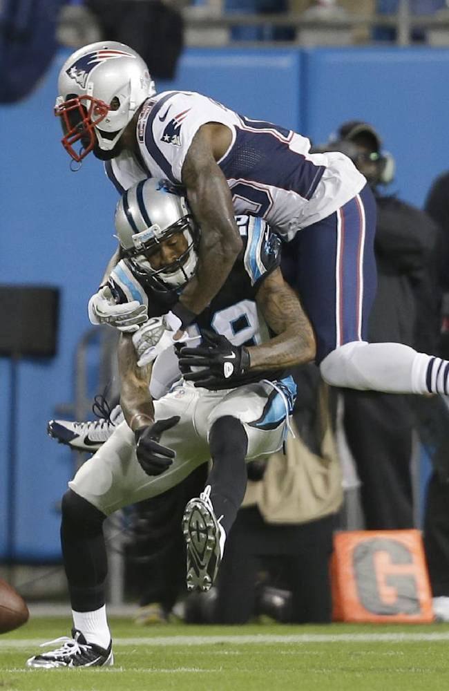 New England Patriots' Kyle Arrington, top, knocks the ball from Carolina Panthers' Ted Ginn, bottom, during the first half of an NFL football game in Charlotte, N.C., Monday, Nov. 18, 2013