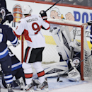 Winnipeg Jets' goaltender Ondrej Pavelec (31) dives into the net to try to stop the shot as Ottawa Senators' Milan Michalek's (9) celebrates his goal as Winnipeg Jets Matt Halischuk (15), Jim Slater (19), Mark Stuart (5) look on during the first period of