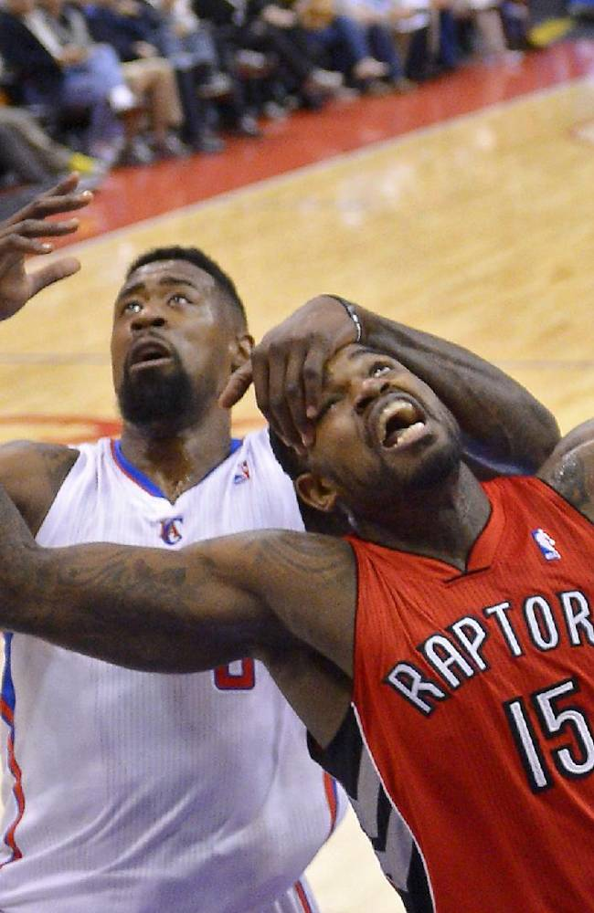 Los Angeles Clippers center DeAndre Jordan, left, and Toronto Raptors forward Amir Johnson battle for a rebound during the first half of an NBA basketball game, Friday, Feb. 7, 2014, in Los Angeles