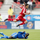 Toronto FC's Gilberto, top, leaps over Montreal Impact's Hassoun Camara after being tackled by the Montreal defender during the first half of an MLS soccer match, Saturday, Oct. 18, 2014, in Toronto The Associated Press