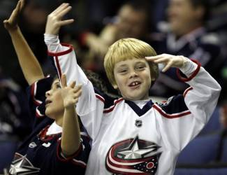 FILE - In this Oct 18, 2011 file photo, Columbus Blue Jackets' fans cheer during an NHL hockey game against the Dallas Stars in Columbus, Ohio. In the wake of a stirring 2013 second-half playoff run that fell just short, the Blue Jackets are seeing an upsurge in interest from fans. Ticket sales have increased, both among longtime buyers and new ones. (AP Photo/Terry Gilliam, File)