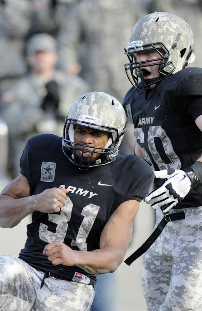 In this Nov. 9, 2103, file photo, Army's Terry Baggett (31) celebrates a touchdown with teammate Justin Gilbert during the first half of an NCAA college football game against Western Kentucky in West Point, N.Y. Army's camouflage style football uniforms are examples of the latest push by the companies that supply athletic equipment to schools to honor the military