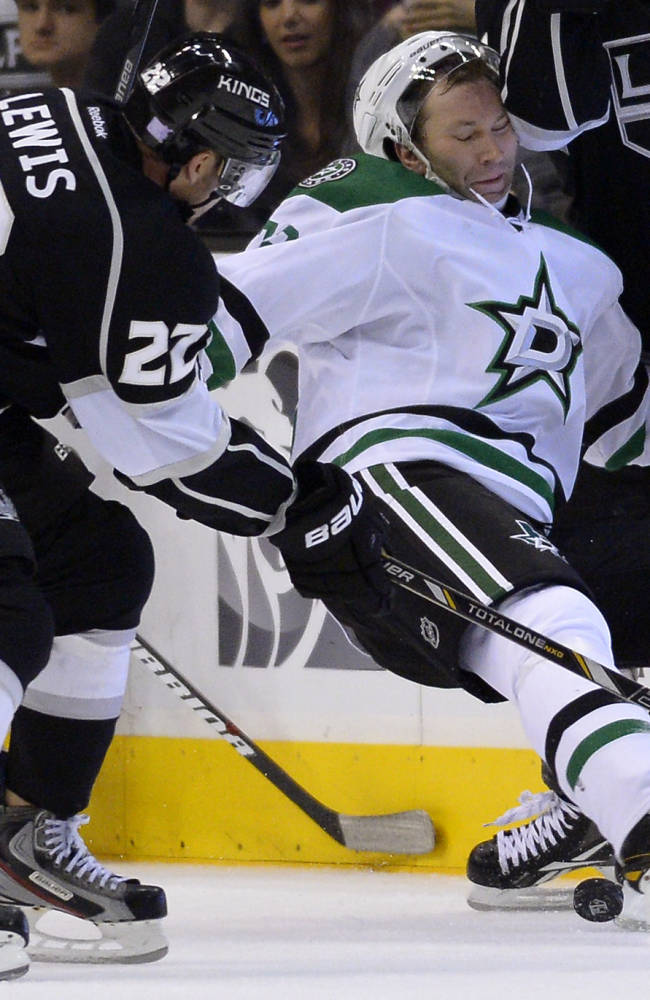 Los Angeles Kings center Trevor Lewis, left, and Dallas Stars right wing Erik Cole battle for the puck during the second period of their NHL hockey game, Saturday, Oct. 19, 2013, in Los Angeles, Calif