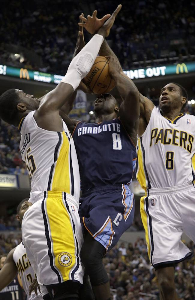 Indiana Pacers defenders, Rasual Butler, right, and Roy Hibbert, left, double-team Charlotte Bobcats guard Ben Gordon during the first half of an NBA basketball game in Indianapolis, Friday, Dec. 13, 2013. Gordon had the ball knocked away on the play