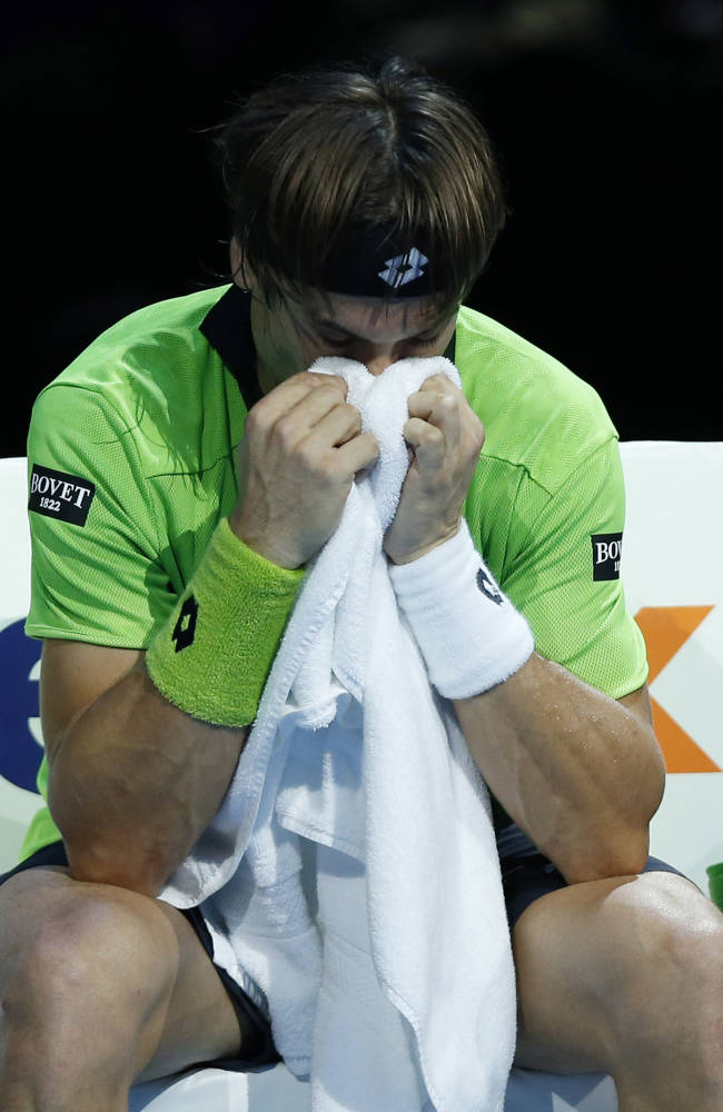David Ferrer of Spain covers his face in a towel during his ATP World Tour Finals single tennis match against Tomas Berdych of Czech Republic at the O2 Arena in London Wednesday, Nov. 6, 2013