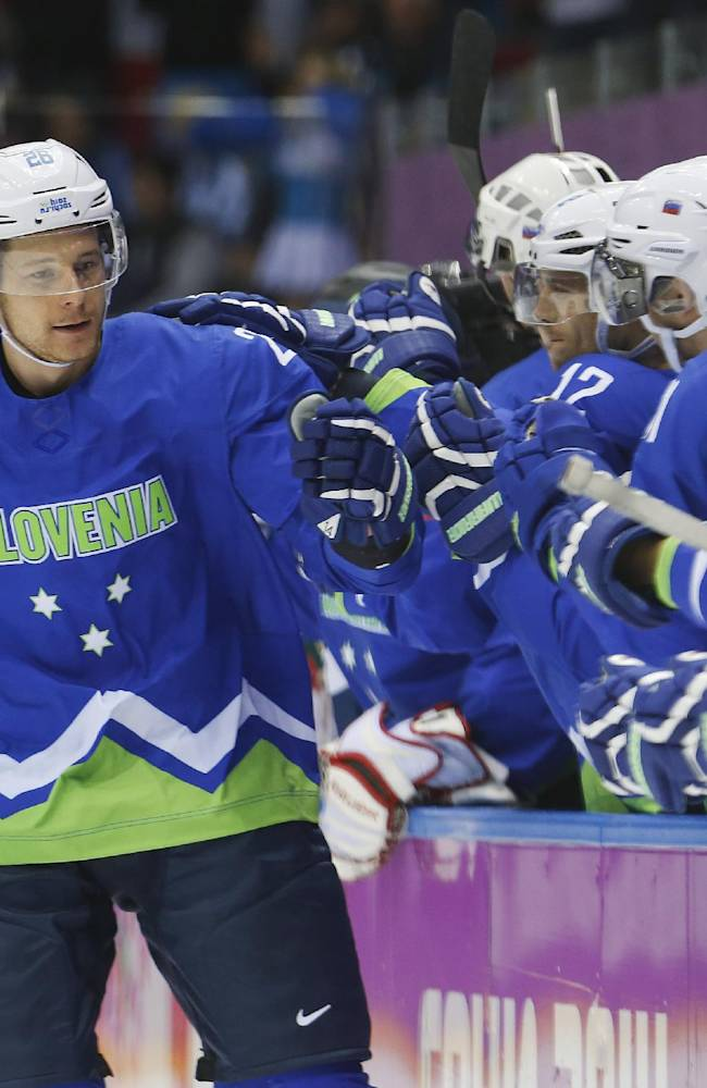 Slovenia forward Jan Urbas is congratulated by teammates after scoring a goal against Austria in the first period of a men's ice hockey game at the 2014 Winter Olympics, Tuesday, Feb. 18, 2014, in Sochi, Russia