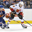 Calgary Flames' Joe Colborne (8) and Edmonton Oilers' Ryan Nugent-Hopkins (93) vie for the puck during the first period of an NHL hockey game Saturday, March 22, 2014, in Edmonton, Alberta The Associated Press