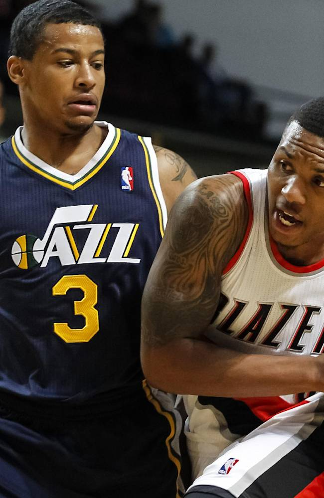 Portland Trail Blazers point guard Damian Lillard, right, drives the ball past Utah Jazz point guard Trey Burke (3) in the first half of a preseason NBA basketball game on Friday, Oct. 11, 2013, in Boise, Idaho