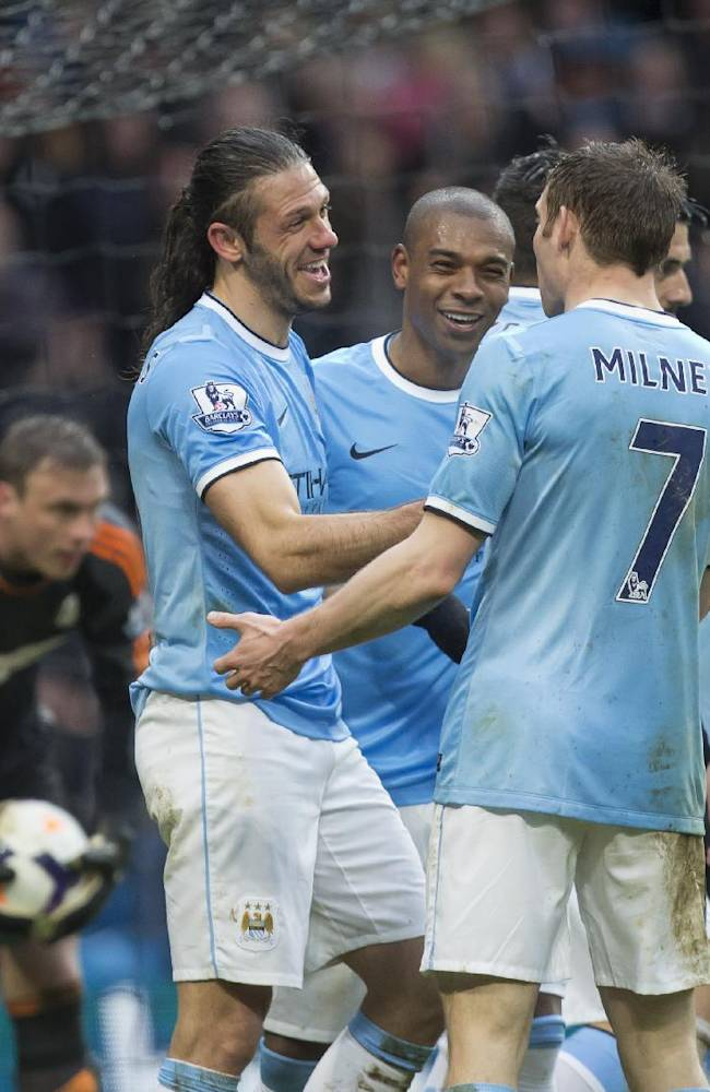 Manchester City's Martin Demichelis, centre left, celebrates with teammates after scoring against Fulham during their English Premier League soccer match at the Etihad Stadium, Manchester, England, Saturday March 22, 2014