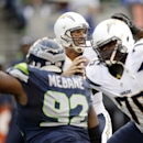 San Diego Chargers quarterback Philip Rivers, center, looks to pass as Chargers offensive tackle D.J. Fluker (76) blocks Seattle Seahawks defensive tackle Brandon Mebane (92) in the first half of a preseason NFL football game against the Seattle Seahawks,