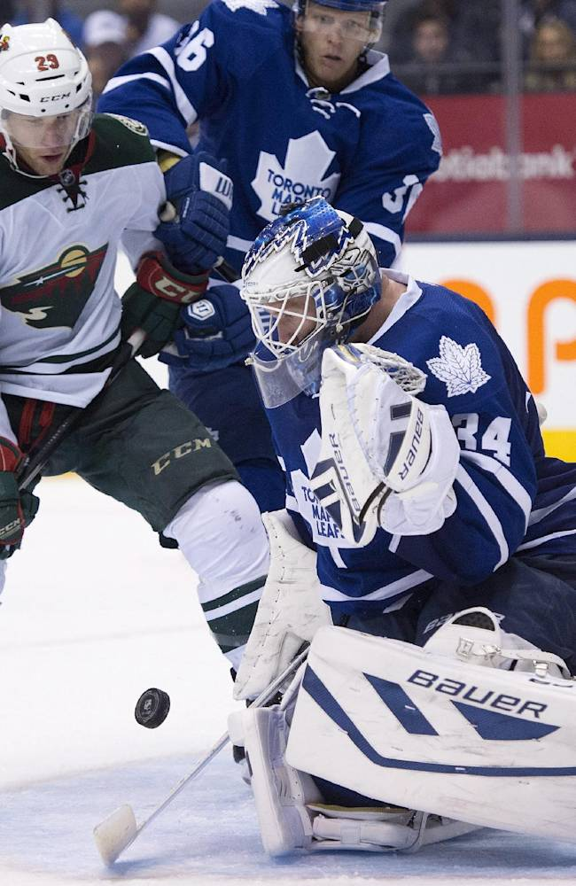 Toronto Maple Leafs goaltender James Reimer makes a save on Minnesota Wild right winger Jason Pominville (29) as defenseman Carl Gunnarsson (36) tries to help defend during the third period of an NHL hockey game in Toronto on Tuesday, Oct. 15, 2013