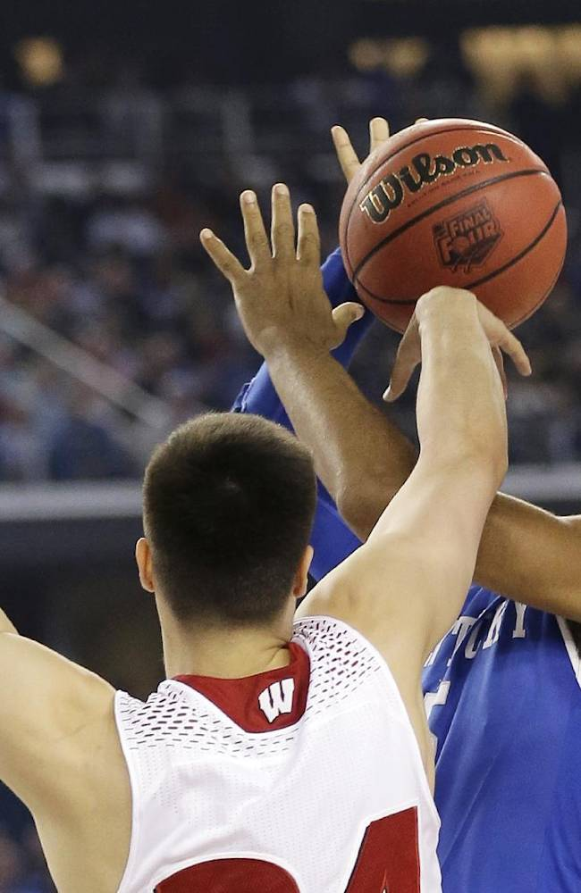 Wisconsin guard Bronson Koenig, left, tries to block a shot by Kentucky guard Andrew Harrison during the first half of an NCAA Final Four tournament college basketball semifinal game Saturday, April 5, 2014, in Arlington, Texas
