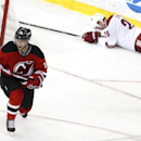 New Jersey Devils center Adam Henrique, left, celebrates after scoring a goal as Phoenix Coyotes defenseman Michael Stone lays on the ice during the third period of an NHL hockey game, Thursday, March 27, 2014, in Newark, N.J. The Coyotes won 3-2 in a sho
