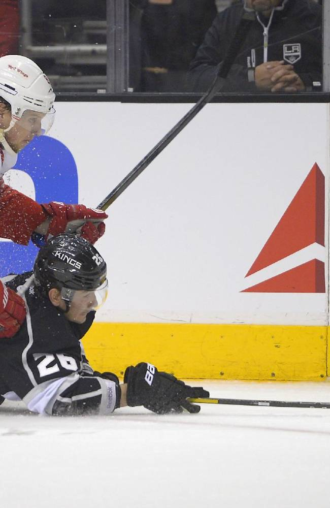 Detroit Red Wings left wing Justin Abdelkader, left, and Los Angeles Kings defenseman Slava Voynov battle for the puck during the first period of an NHL hockey game, Saturday, Jan. 11, 2014, in Los Angeles